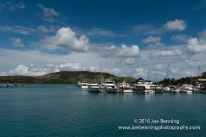 Ships anchored at the Hamilton Island Yacht Club. Jet skiers glide by in the distance.