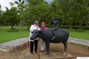 Mary Anne and Ricki pose by a statue of the Buddha on a cow, near Borobudur Temple.