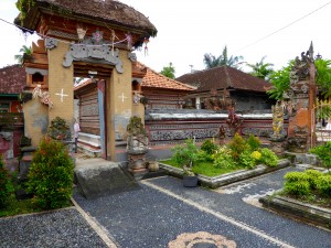 the entry to a family compound in a village in Bali; entry is on the left, on the right are gardens which line the road; toilets are a new addition to village homes in Bali