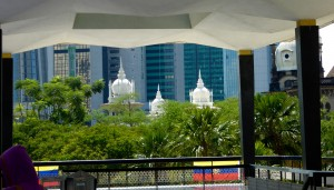 a view of KL showing the old and new; mosque roofs in front of high rise office towers