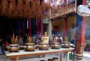 A Buddhist temple in Chinatown; you can see joss sticks in the front, and spiral incense coils hanging from the ceiling, with purple and red papers containing the petitions requesting prayers.  We saw many tourists but also many locals worshipping at the temple.  Because so many people came to Vietnam by boat, this temple is dedicated to the gods and goddesses of water travel.  There is also a shrine to the god of business (who rewards his worshippers with prosperity).  The temple is open air, and you can see a plastic cover over the fan in the  upper right corner.