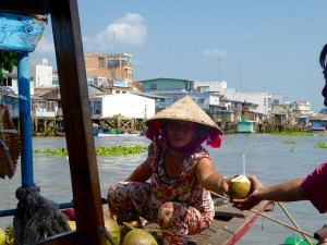 On the Mekong River at the floating market a lady cuts open a coconut and offers it to our guide for a drink; notice how the vendor squats low - we saw this everywhere as the way people hang out (not sitting or standing).