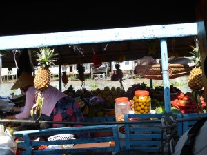 another boat at the floating market, this one filled with fruit; the vendor is bending down in the left side of the picture, wearing the traditional conical hat.  A husband and wife will live on the boat, getting replenishment inventory from their farms/gardens, and returning to their homes on land after they are done selling the crops.