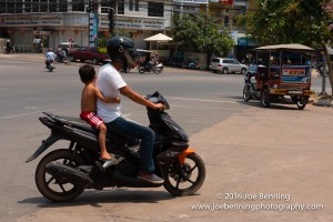 A small boy clinging to the driver of a motorbike in Cambodia