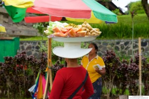 Woman balancing fruits and vegetables on her head in the market in Bali, Indonesia.