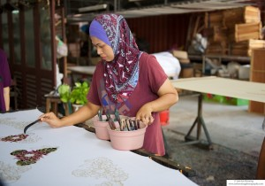 Photo of a woman painting in a stencil in a Batik factory in Penang, Malaysia
