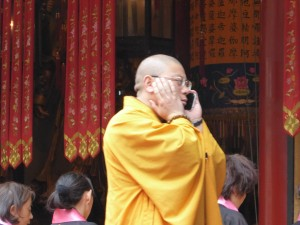 a monk at the service takes a quick call