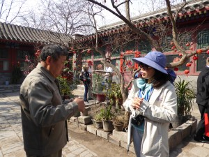 the owner of the Hutong house talks with a guest from the ship in the courtyard/quadrangle