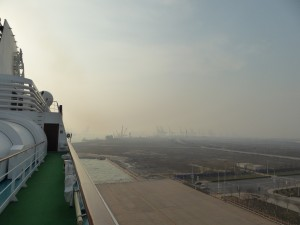 a shot from the top of the ship - if you peer through the smog you can see just a few of the big machines at the port