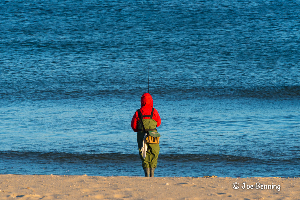 A winter fisherman waits patiently on the beach in Spring Lake